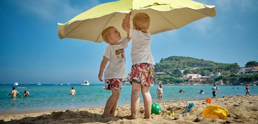 niños en la playa con sombrilla